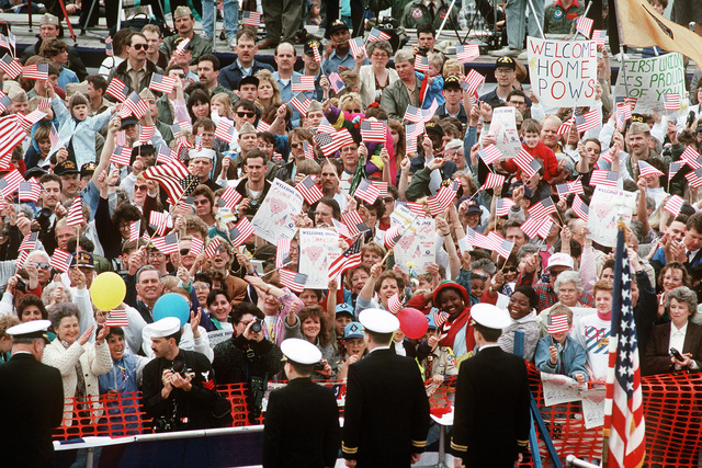 A crowd of well-wishers welcomes LT. Jeffrey Zaun, LT. Lawrence Slade, and LT. Robert Wetzel during a ceremony in their honor. The three Navy pilots' aircraft were shot down over Iraq during Operation Desert Storm and the men held as prisoners of war until their release on March 4th