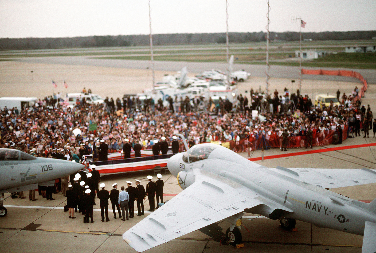 A Fighter Squadron 101 (VF-101) F-14A Tomcat aircraft, an A-6 Intruder aircraft and a Fleet Logistics Support Squadron 56 (VR-56) C-9 Nightingale aircraft provide the backdrop as a crowd of well-wishers welcomes LT. Robert Wetzel, LT. Lawrence Slade, and LT. Jeffrey Zaun during a ceremony in their honor. The three Navy pilots' aircraft were shot down over Iraq during Operation Desert Storm and the men held as prisoners of war until their release on March 4th