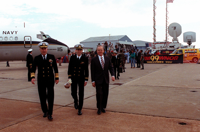 LT. Robert Wetzel walks between CHIEF of Naval Operations Adm. Frank B. Kelso II, left, and Secretary of the Navy H. Lawrence Garrett III following a ceremony held in honor of Wetzel and two other former prisoners of war (POWs). Wetzel, LT. Jeffrey Zaun and LT. Lawrence Slade had been shot down during Operation Desert Storm and were among the first group of ten coalition POWs released by Iraq on March 4th.