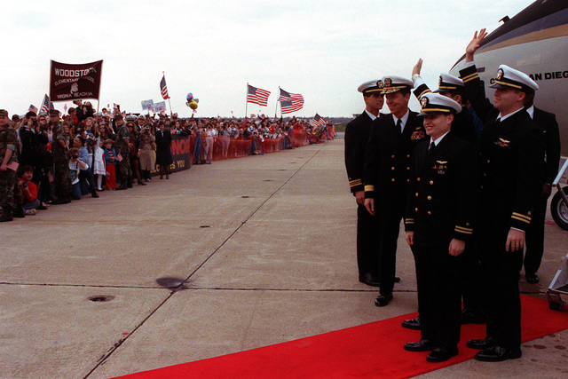Rear Adm. Paul W. Parcells, second from left, commander, Tactical Wings, Atlantic, stands with LT. Robert Wetzel, LT. Jeffrey Zaun, second from right, and LT. Lawrence Slade, right, as they wave to the crowd gathered for a ceremony to honor the three former prisoners of war (POWs). The three lieutenants and had been shot down during Operation Desert Storm and were among the first group of ten coalition POWs released by Iraq on March 4th.