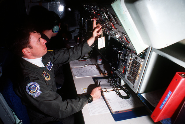 """CAPT. Tom Neiss, a launch control officer with the 2nd Airborne Command and Control Squadron, 55th Strategic Reconnaissance Wing, works in the battle staff compartment aboard an EC-135 Stratolifter """"Looking Glass"""" aircraft during """"Glory trip 143GB."""" Glory Trip 143GB is the first remote launch of a silo-housed Minuteman III missile by an aircraft based at Offutt Air Force Base, Neb. The missile will be launched from Vandenberg Air Force Base, Calif"""