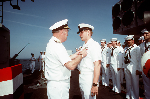 CHIEF of Naval Operations Adm. Frank B. Kelso II pins an award on a chief petty officer during a ceremony aboard the guided missile destroyer USS MACDONOUGH (DDG-39). Kelso is visiting the MACDONOUGH as the ship nears Naval Station, Charleston, S.C., following its deployment to the Persian Gulf region for Operation Desert Shield and Operation Desert Storm