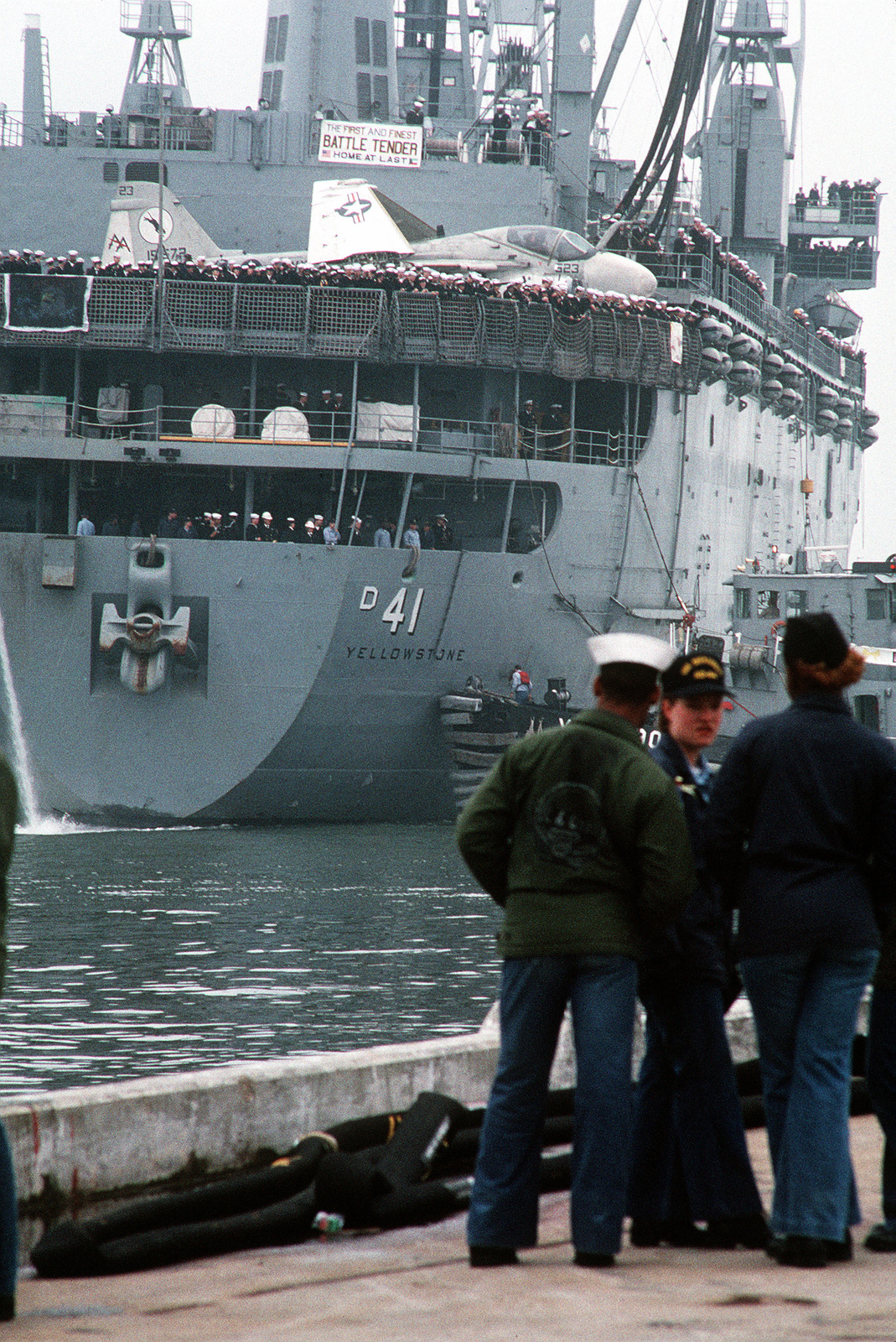 Line handlers stand by as a large harbor tug helps bring the destroyer tender USS YELLOWSTONE (AD-41) alongside the pier. The YELLOWSTONE is returning to Norfolk following its deployment to the Persian Gulf region in support of Operation Desert Shield and Operation Desert Storm. An Attack Squadron 35 (VA-35) A-6E Intruder aircraft sits on the YELLOWSTONE's helicopter deck