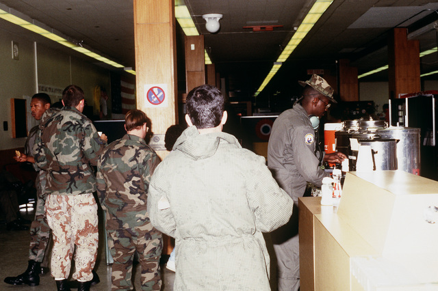 U.S. military personnel enjoy refreshments provided by the United Service Organizations and base residents during a stopover at the air station. The troops are returning from serving in the Persian Gulf during Operation Desert Storm