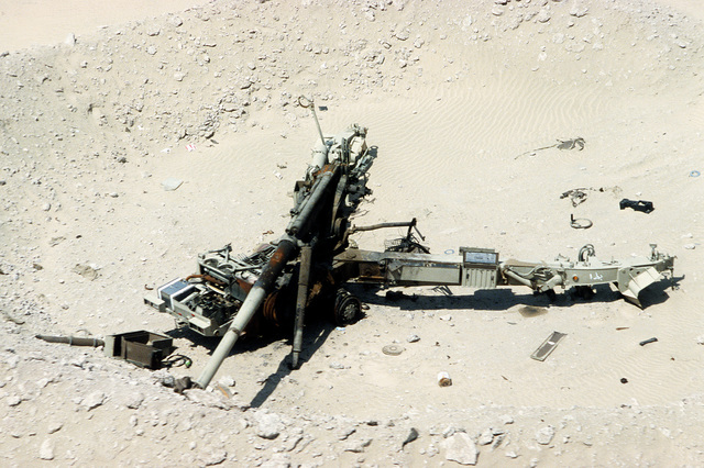 A demolished Iraqi artillery piece lies in the sand in the aftermath of Operation Desert Storm