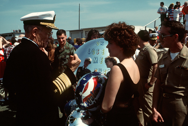 Adm. Leon A. Edney, commander-in-chief, U.S. Atlantic Command/Supreme Allied Commander Atlantic, talks with a woman while waiting to greet naval aviators returning from Operation Desert Storm. Carrier AIR WING 3 (CVW-3), embarked aboard the aircraft carrier USS JOHN F. KENNEDY (CV-67), is returning today