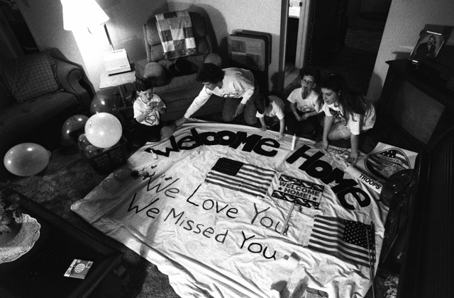 The ombudsman for the battleship USS WISCONSIN (BB-64) and her children prepare a welcome-home banner for the crew of the vessel. The WISCONSIN is scheduled to return to Naval Station, Norfolk, on March 28th following deployment in the Persian Gulf area during Operation Desert Storm