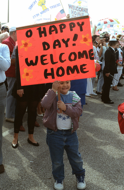 A child holds a sign welcoming crew members of five ships from the aircraft carrier USS SARATOGA (CV-60) battle group upon their arrival at the station. The vessels have returned from the Persian Gulf area after being deployed during Operation Desert Storm