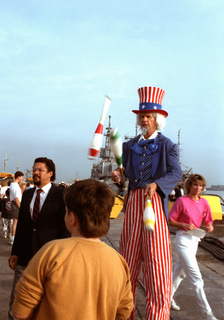 A juggler dressed as Uncle Sam entertains the crowd waiting for the arrival of a ship returning from the Persian Gulf region. Five ships of the aircraft USS SARATOGA (CV-60) battle group are coming home to Mayport today after serving in the Persian Gulf region during Operation Desert Shield and Operation Desert Storm