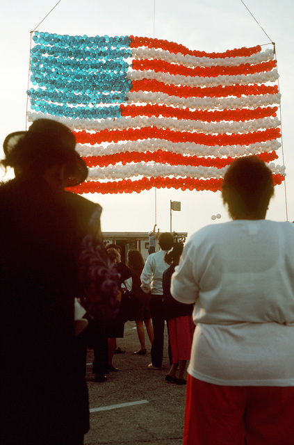 A large American flag made of balloons is hoisted over the crowd gathered on the pier to welcome the aircraft carrier USS SARATOGA (CV-60). The SARATOGA and its battle group are returning to Mayport following their deployment to the Persian Gulf region for Operation Desert Shield and Operation Desert Storm