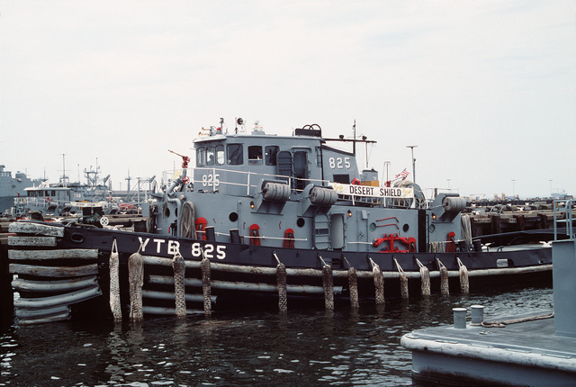 A port bow view of the large harbor tug Wathena (YTB-825) tied up at the service craft pier awaiting to assist with the docking of a large number of ships returning today from Operation Desert Shield/Storm