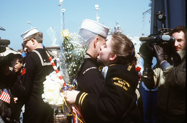 A sailor from the guided missile frigate USS SAMUEL B. ROBERTS (FFG-58) embraces his wife as television cameras record their reunion. The SAMUEL B. ROBERTS has returned to Newport following its deployment to the Persian Gulf region for Operation Desert Shield and Operation Desert Storm