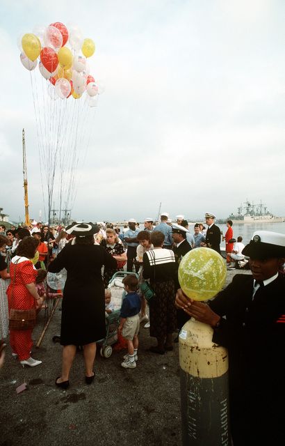 A sailor prepares helium-filled balloons for the crowd gathered on a pier to wait for the arrival of one of the ships of the aircraft carrier USS SARAGTOGA (CV-60) battle group. The battle group is returning to Mayport following their deployment to the Persian Gulf region for Operation Desert Shield and Operation Desert Storm