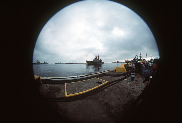 A view of the guided missile cruiser USS PHILIPPINE SEA (CG-58), followed by the frigate USS W. S. SIMS (FF-1059), approaching port as seen through a fish eye camera lens. The PHILIPPINE SEA is one of five ships of the aircraft carrier USS SARATOGA (CV-60) battle group that is returning to Mayport following deployment in the Persian Gulf area during Operation Desert Storm