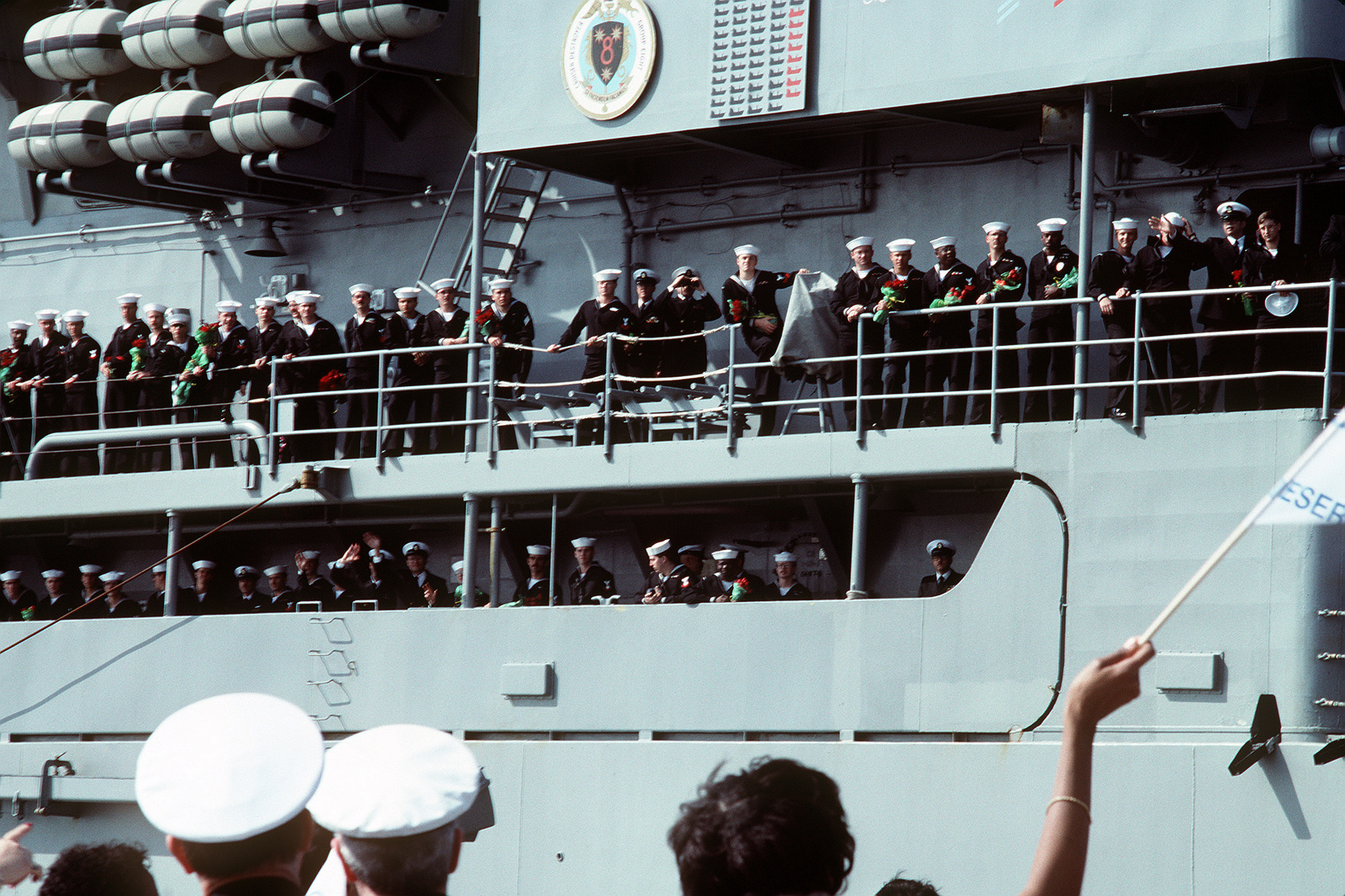 Crew members stand at the railing aboard the nuclear-powered guided missile cruiser USS MISSISSIPPI (CGN-40) as they look for their loved ones in the crowd on the pier. Ships of the aircraft carrier USS JOHN F. KENNEDY (CV-67) battle group are returning to Norfolk following deployment in the Persian Gulf area during Operation Desert Storm