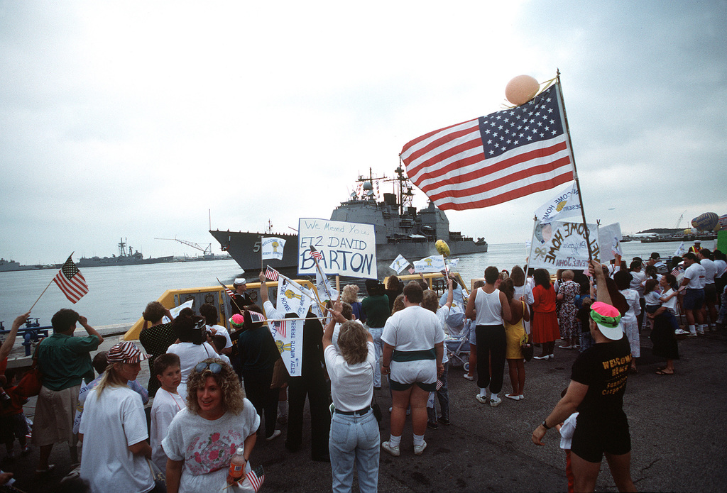 Crowd members display flags and banners as they welcome the crew of