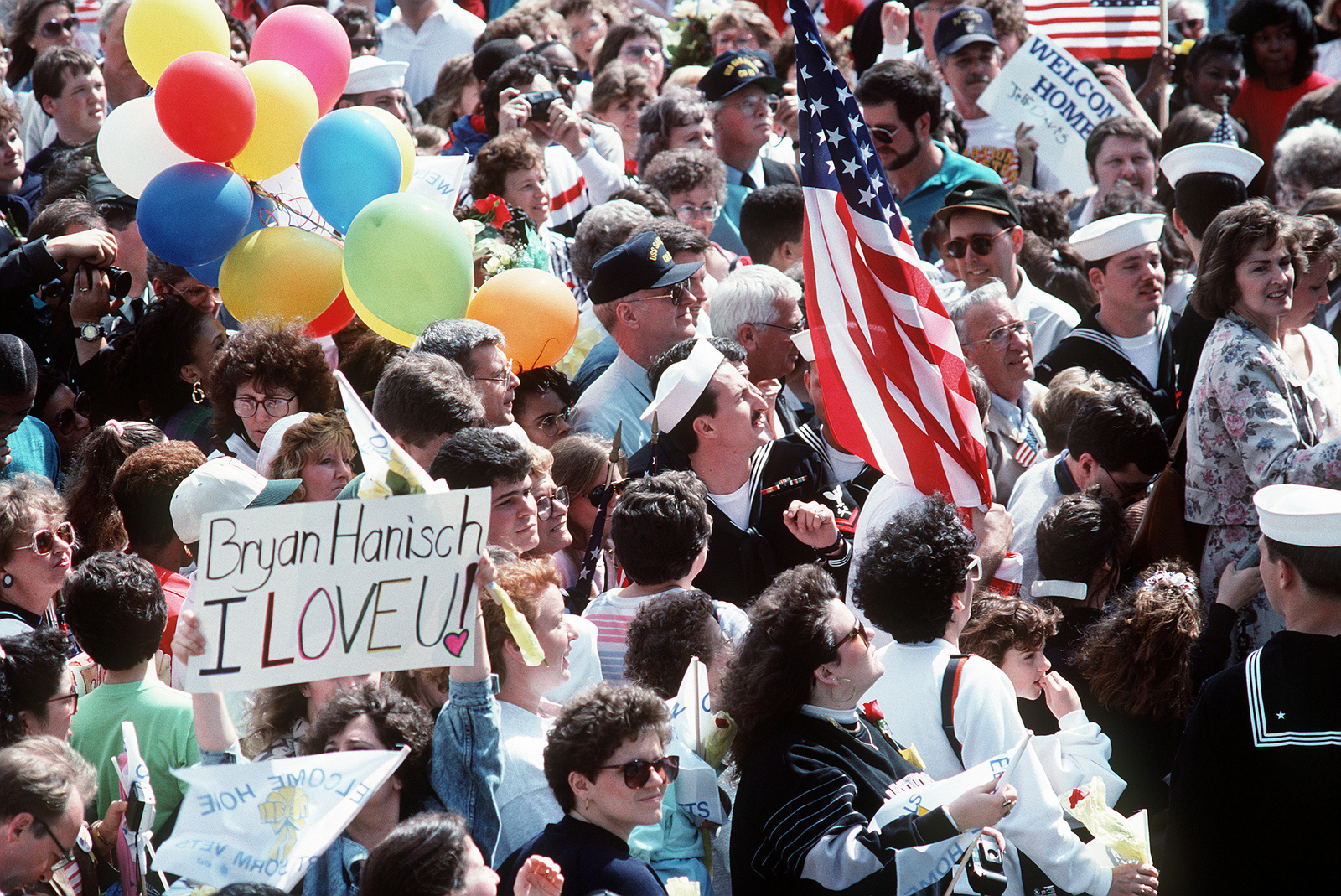 Crowd members on the pier hold banners, balloons and flags as they look for their loved ones aboard ships of the aircraft carrier USS JOHN F. KENNEDY (CV-67) battle group. The vessels are returning to Norfolk following deployment in the Persian Gulf area during Operation Desert Storm