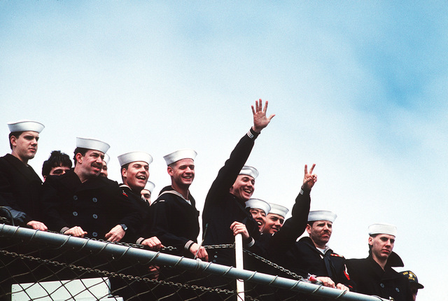 Sailors on board the amphibious assault ship USS Inchon (LPH-12) wave to family and love ones while the ship is still being maneuvered pierside upon return from Operation Desert Storm