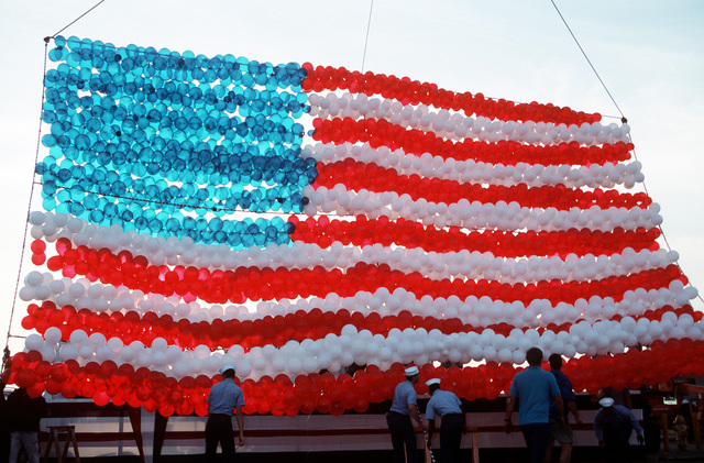 Sailors set up a large American flag made of balloons on the pier to welcome the aircraft carrier USS SARATOGA (CV-60). The SARATOGA and the ships of its battle group are returning to Mayport following their deployment to the Persian Gulf region for Operation Desert Shield and Operation Desert Storm