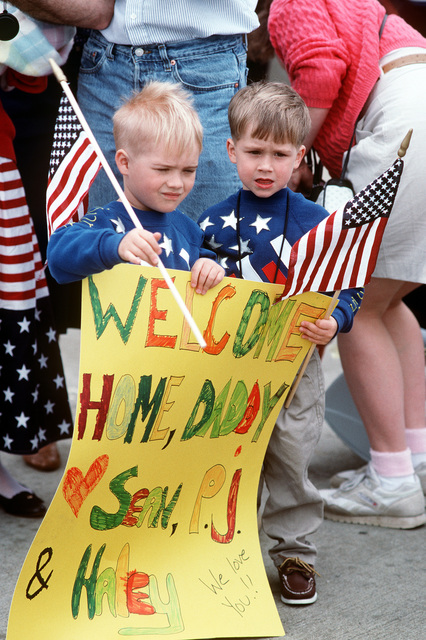 The children of a sailor hold flags and a sign as they wait on the pier for the arrival of their father. Eight ships are returning to Norfolk today following their deployment to the Persian Gulf region for Operation Desert Shield and Operation Desert Storm