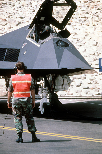 STAFF SGT. David Owings, crew chief, communicates with MAJ. Joe Bowley, a fighter pilot with the 37th Tactical Fighter Wing, as Bowley performs a preflight check of his F-117 Stealth Fighter aircraft in preparation for redeployment to the United States in the aftermath of Operation Desert Storm.