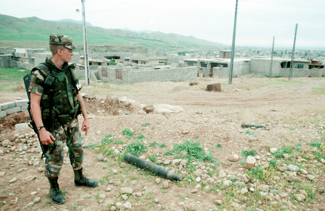 2LT Christopher Walton of the Army's 284th Military Police Company looks at a pair of discarded artillery rounds found near an abandoned Iraqi gun emplacement. U.S. and coalition troops are in Zakhu as part of Operation Provide Comfort, a multinational effort to aid Kurdish refugees in northern Iraq and southern Turkey