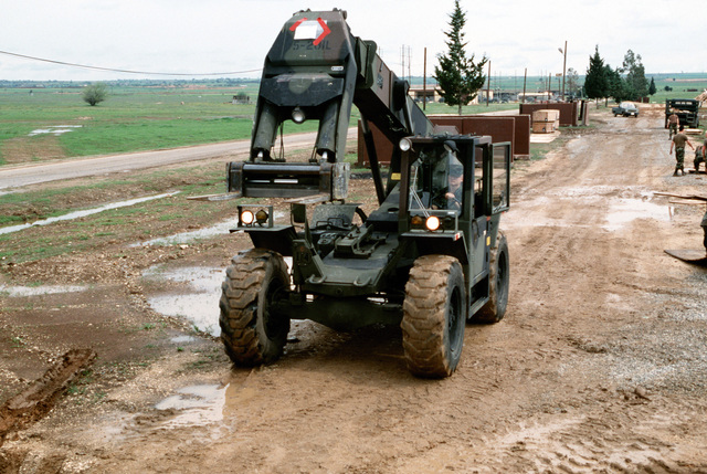 A forklift is driven down a dirt road during construction of a tent city living area to house personnel deployed in support of Operation Provide Comfort.