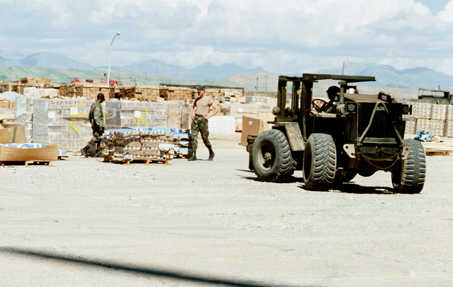 A forklift positions stacks of supplies for loading aboard helicopters. The material will be delivered to Kurdish refugees as part of Operation Provide Comfort, an Allied effort to aid the refugees who fled from the forces of Saddam Hussein in northern Iraq