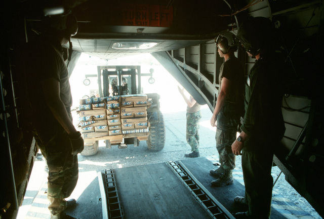 A forklift positions supplies for loading into a CH-53E Super Stallion helicopter. The material will be delivered to Kurdish refugees as part of Operation Provide Comfort, an Allied effort to aid the refugees who fled from the forces of Saddam Hussein in northern Iraq