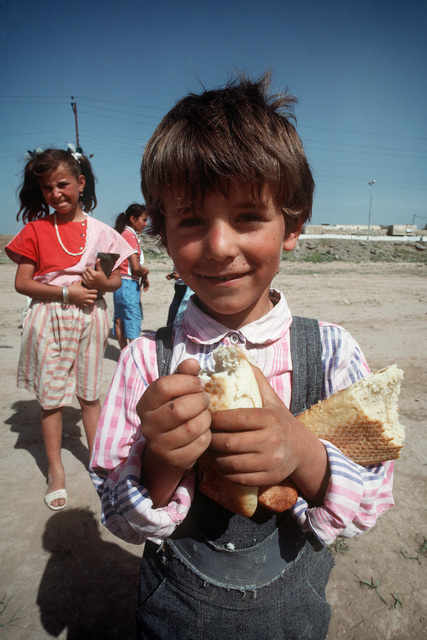A Kurdish boy eats a piece of bread that was given to him by British soldiers on the outskirts of the city. U.S. and coalition troops are in Zakhu as part of Operation Provide Comfort, a multinational effort to aid Kurdish refugees in northern Iraq and southern Turkey