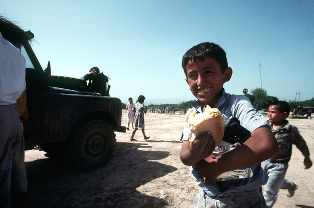 A Kurdish boy smiles as he carries the bread and field rations that were given to him by British soldiers on the outskirts of the city. U.S. and coalition troops are in Zakhu as part of Operation Provide Comfort, a multinational effort to aid Kurdish refugees in northern Iraq and southern Turkey