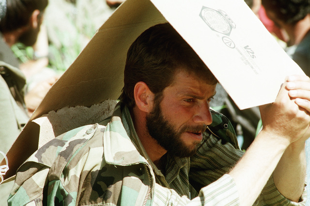 A Kurdish man shades his face with a piece of cardboard as he sits in the grass after arriving at a refugee camp near Zakhu, Iraq. U.S. and allied troops established the camp as part of Operation Provide Comfort, a multinational effort to aid the thousands of Kurds who fled their homes after fighting broke out between Kurdish groups and Iraqi government forces following Operation Desert Storm