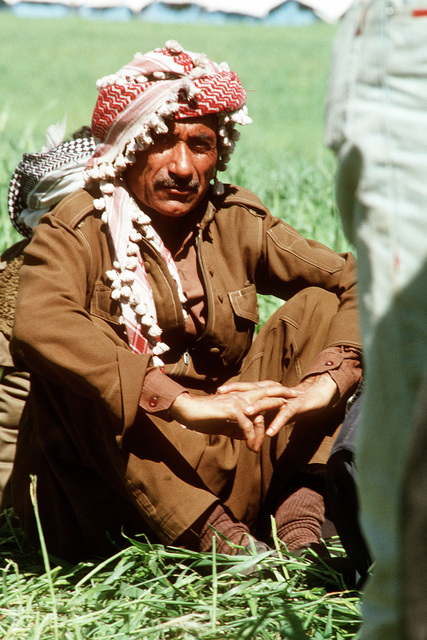 A Kurdish man sits in the grass after arriving at a refugee camp near Zakhu, Iraq. U.S. and allied troops established the camp as part of Operation Provide Comfort, a multinational effort to aid the thousands of Kurds who fled their homes after fighting broke out between Kurdish groups and Iraqi government forces following Operation Desert Storm