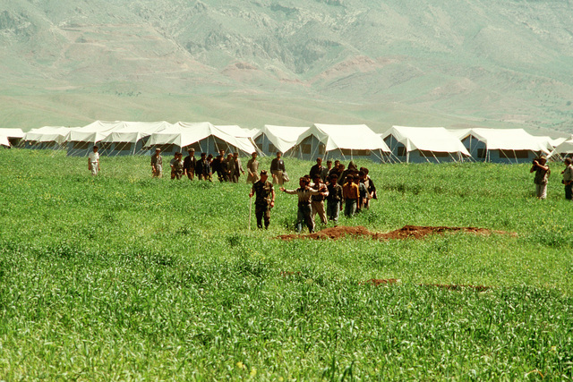 A Marine leads a group of Kurdish men on a tour of a refugee camp near Zakhu, Iraq. U.S. and allied troops established the camp as part of Operation Provide Comfort, a multination effort to aid the thousands of Kurds who fled their homes after fighting broke out between Kurdish groups and Iraqi government forces following Operation Desert Storm
