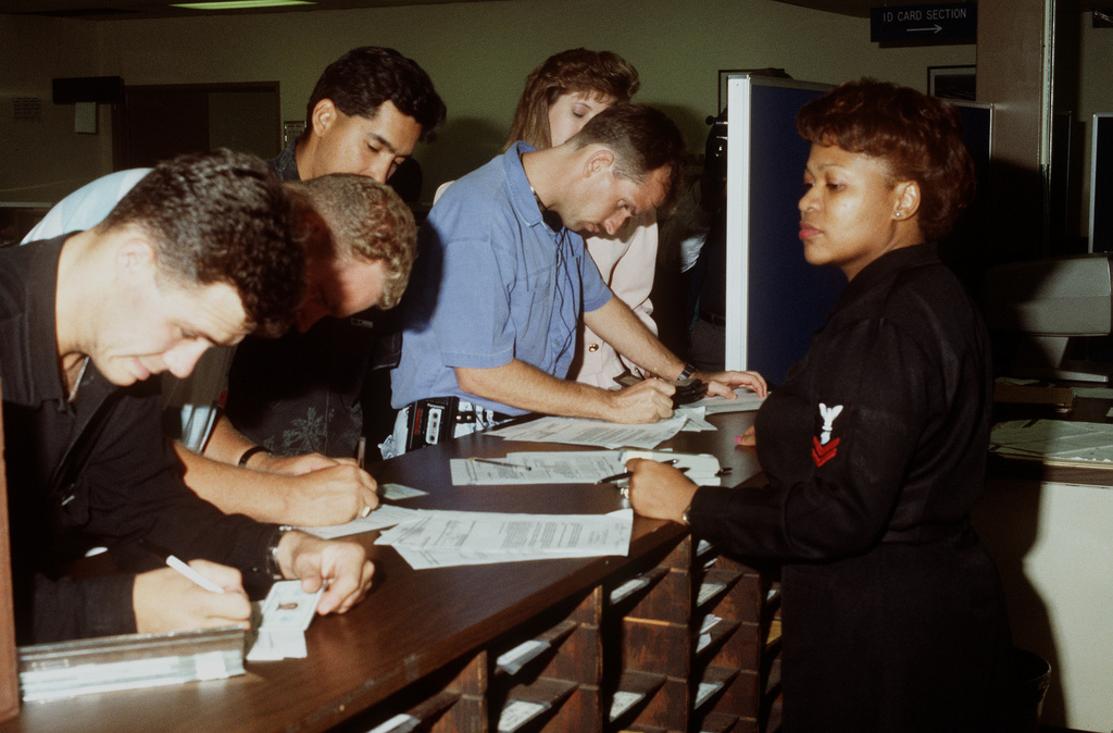A member of the Naval Reserve Readiness Command 20 (REDCOM-20) personnel support detachment watches as several Navy reservists fill out forms. The reservists have just returned from duty in the Persian Gulf region following Operation Desert Storm