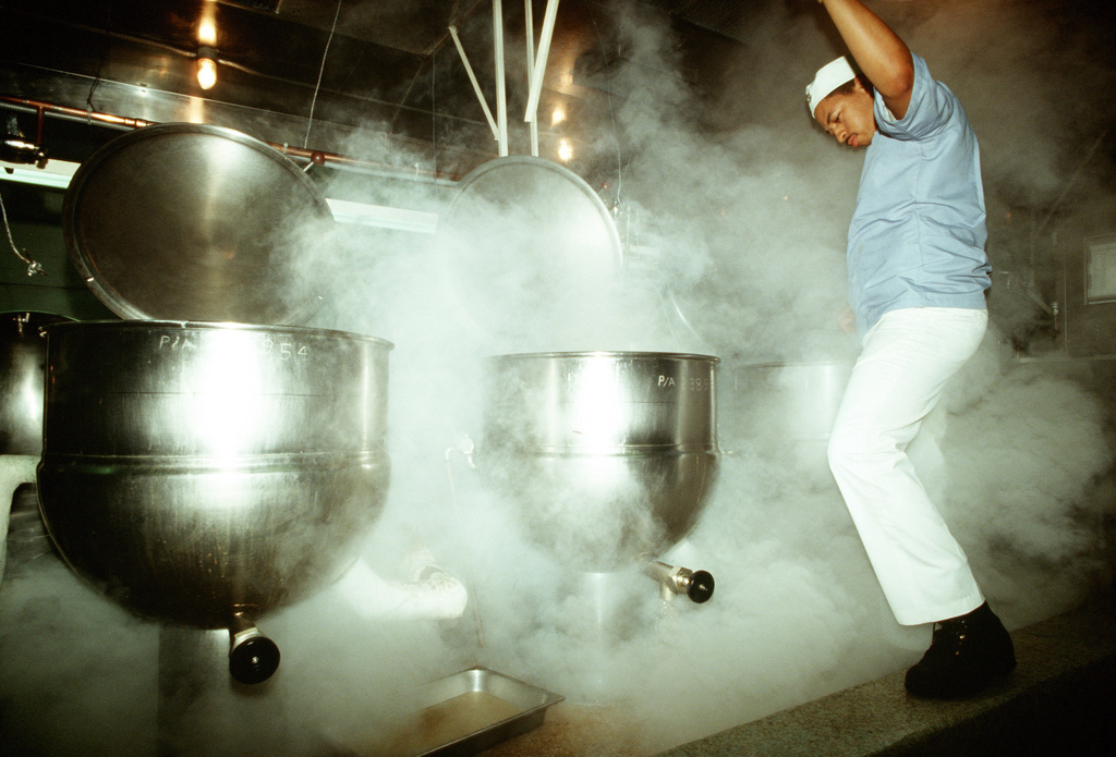A mess management specialist is surrounded by steam as he cleans cooking gear in a galley