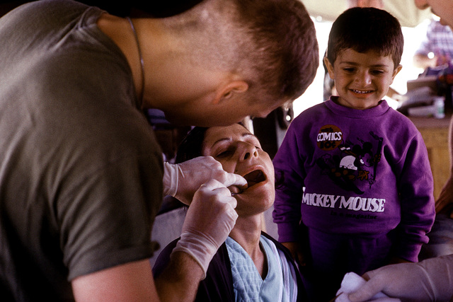 A Navy dentist examines a Kurdish woman in a medical tent during Operation Provide Comfort, a multinational effort to aid Kurdish refugees in southern Turkey and northern Iraq
