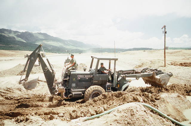 A Seabee operates the backhoe attached to the rear of a loader as members of an air detachment from Naval Mobile Construction Battalion 133 (NMCB-133) repair the runway at an Iraqi airfield. The Seabees are repairing the airfield, which had been under construction prior to the start of the Persian Gulf war, to allow relief supplies to be flown in for nearby Kurdish refugees as part of Operation Provide Comfort