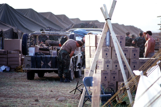 A serviceman prepares to unload gasoline cans from the back of a modified M-151 1/4-ton light utility vehicle after arriving at the humanitarian services support base established for Operation Provide Comfort, a multinational effort to aid Kurdish refugees in northern Iraq and southern Turkey