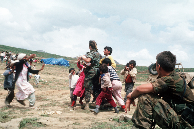 A soldier distributes food to Kurdish refugee children as part of Operation Provide Comfort, an Allied effort to aid the refugees who fled the forces of Saddam Hussein in Northern Iraq