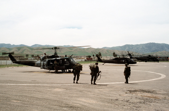A UH-1N Iroquois, UH-60 Black Hawk and CH-53E Super Stallion helicopter stand in line at a helicopter landing area near a Kurdish refugee camp. The helicopters are being used during Operation Provide Comfort, an Allied effort to aid the refugees who fled from the forces of Saddam Hussein in northern Iraq