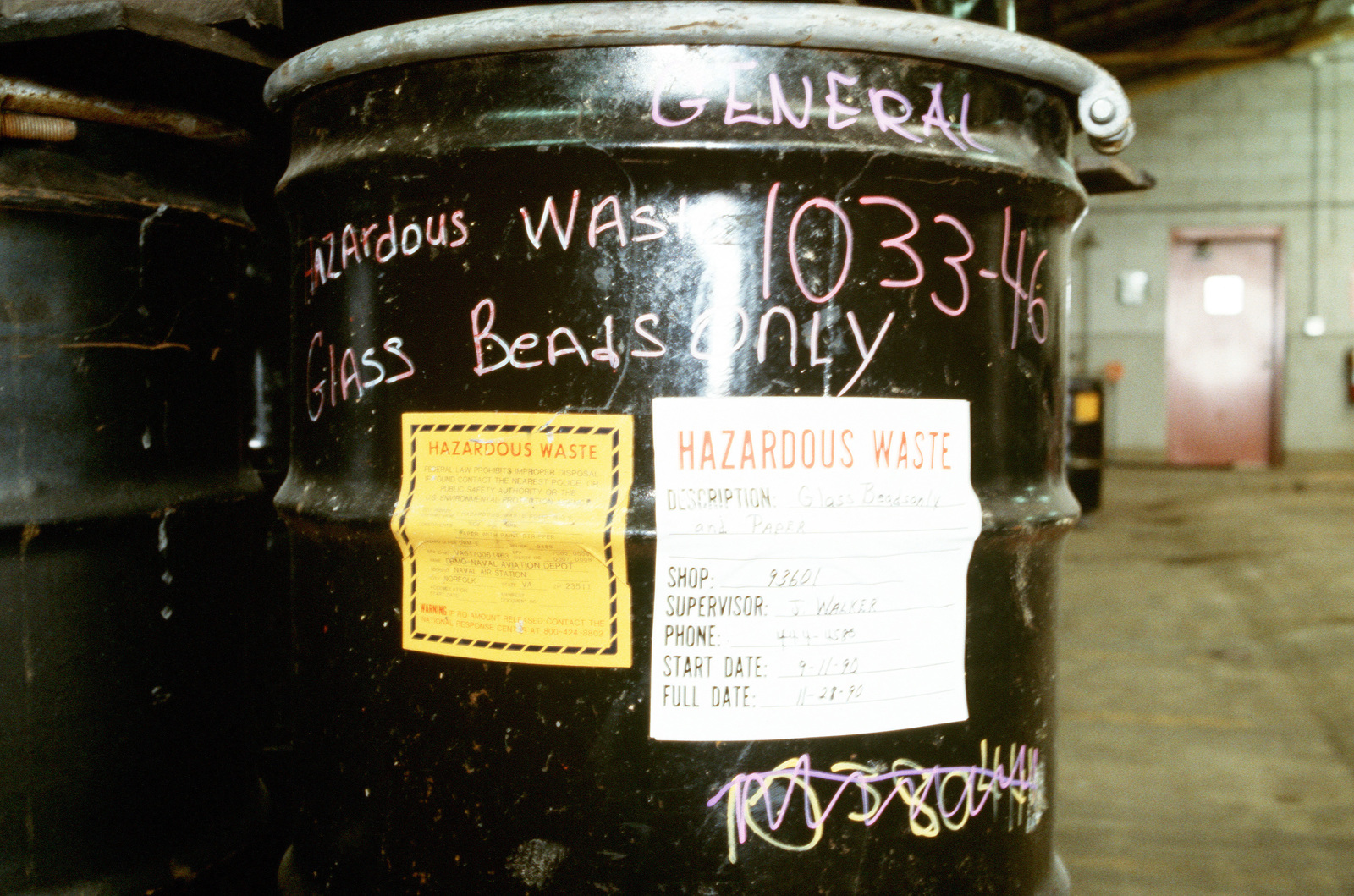 A view of the documentation affixed to the side of a hazardous waste barrel in a warehouse