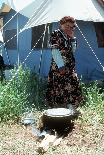 A young Kurdish refugee tends a cooking fire outside her family's tent in northern Iraq. U.S. and coalition forces are setting up shelter and providing food to the refugees as part of Operation Provide Comfort