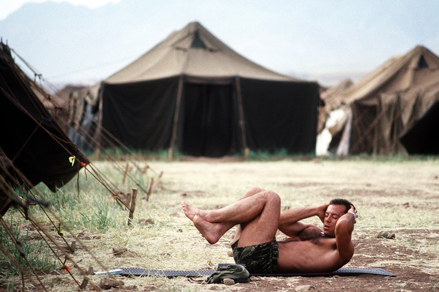 An off-duty serviceman exercises outside his tent while assigned to the humanitarian services support base established for Operation Provide Comfort, a multinational effort to aid Kurdish refugees in northern Iraq and southern Turkey