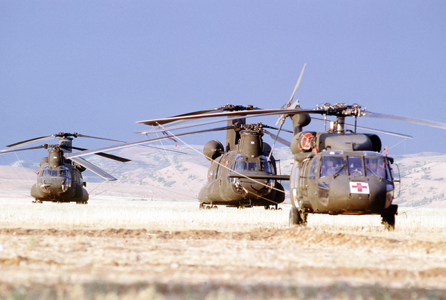 An UH-60 Black Hawk helicopter, foreground, and two CH-47 Chinook helicopters stand in a field near a tent city housing Kurdish refugees. The camp was established as part of Operation Provide Comfort, an Allied effort to aid the refugees who fled the forces of Saddam Hussein in northern Iraq