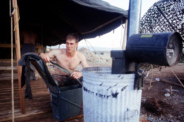 CPL Michael J. Knapp of the 24th Marine Expeditionary Unit (24th MEU) washes his clothes in an ammunition can while assigned to the humanitarian services support base established for Operation Provide Comfort, a multinational effort to aid Kurdish refugees in northern Iraq and southern Turkey