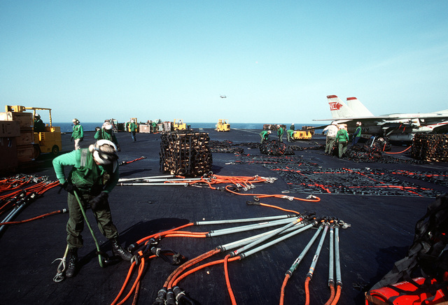 Flight deck crewmen aboard the aircraft carrier USS RANGER (CV-61) gather up hoisting slings, pendants and cargo nets to return them to the replenishment oiler USS KANSAS CITY (AOR-3) following a vertical replenishment. The ships are on station in the Persian Gulf region following Operation Desert Storm