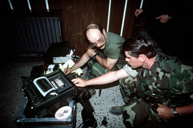 Journalist 1ST Class J. D. DiMattio, left, and Photographer's Mate 2nd Class Gregory Milota coordinate information on a story for Navy Broadcasting Service. The men are in Zakhu covering Operation Provide Comfort, an Allied effort to aid Kurdish refugees who fled from the forces of Saddam Hussien in northern Iraq