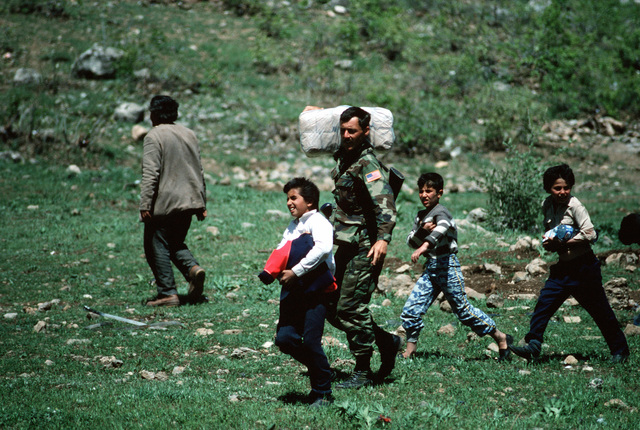Kurdish children follow a U.S. soldier as he moves supplies from a helicopter landing zone to a refugee camp. The material is being provided as part of Operation Provide Comfort, an Allied effort to aid the refugees who fled from the forces of Saddam Hussein in northern Iraq