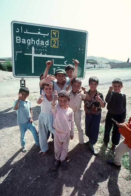 """Kurdish children give the """"thumbs up"""" to a photographer as they stand near a road sign on the edge of the city. U.S. and coalition troops are in Zakhu as part of Operation Provide Comfort, a multinational effort to aid Kurdish refugees in northern Iraq and southern Turkey"""